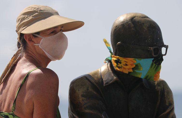 Uma mulher posa para uma foto ao lado da estátua do escritor brasileiro Carlos Drummond de Andrade que usa uma máscara protetora no primeiro dia de uso obrigatório de máscaras na cidade do Rio de Janeiro, em meio ao surto de doença por coronavírus (COVID-19), na praia de Copacabana